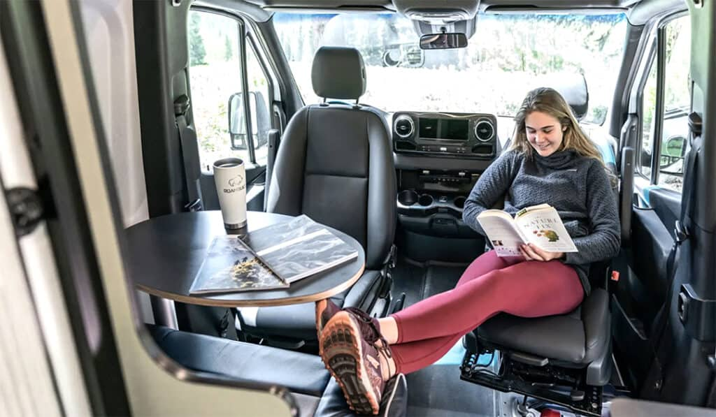 Woman reads book in small drivable RV.