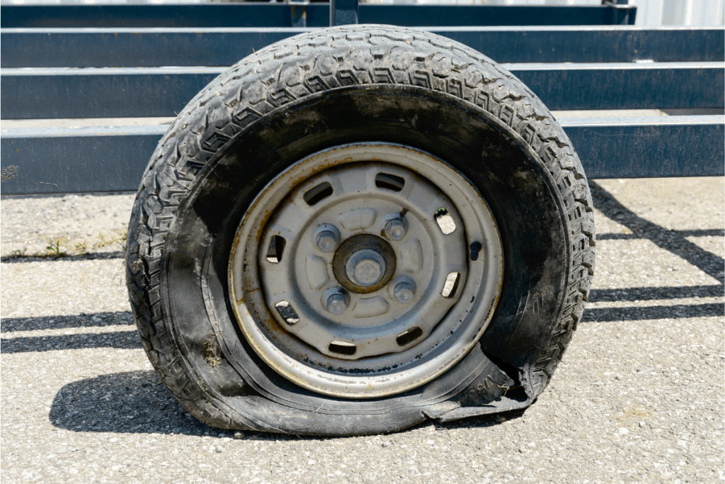 Heavily damaged tire on rim attached to small trailer.