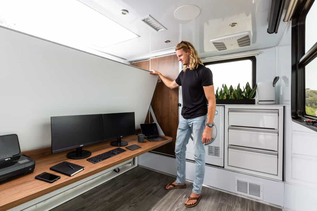 Matt Hoffman of living vehicle demonstrates an RV mobile office innovation.