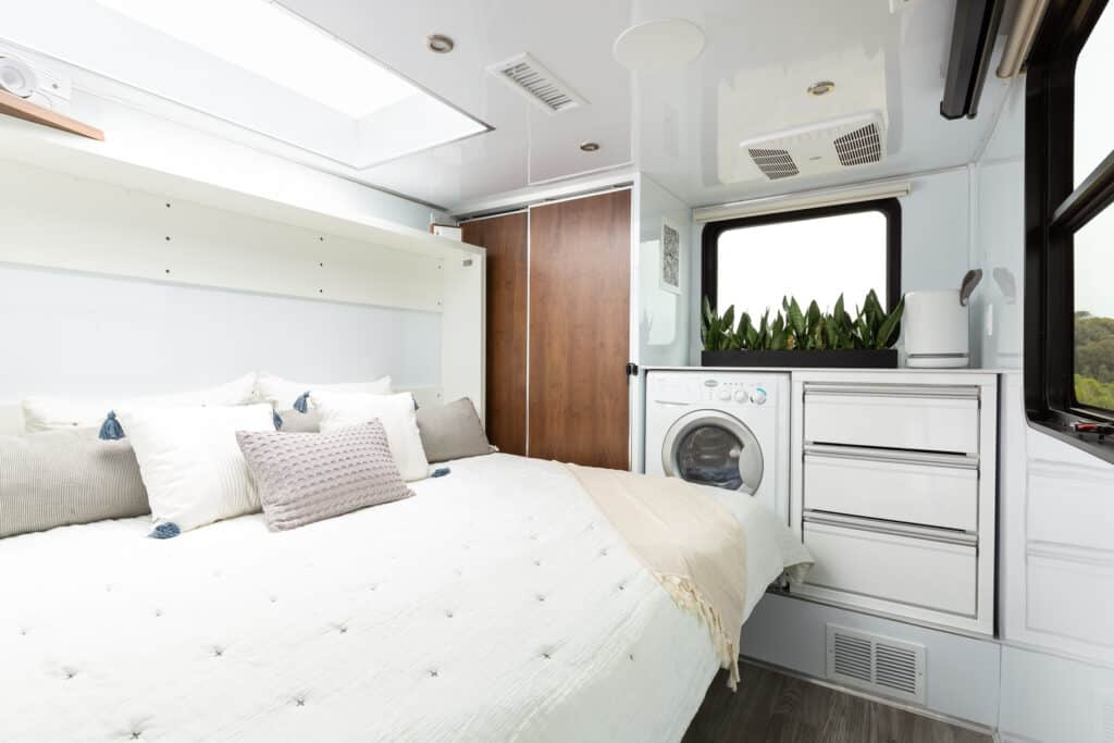A full sized queen bed hides an entire home office that never needs to be broken down - Photo: Living Vehicle