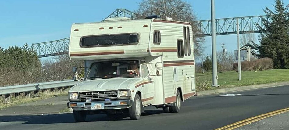 older class C RV in white and brown