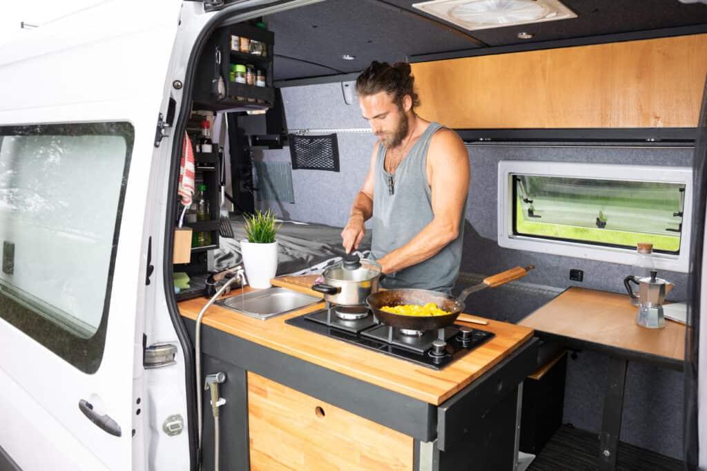 tall man cooking in camper van