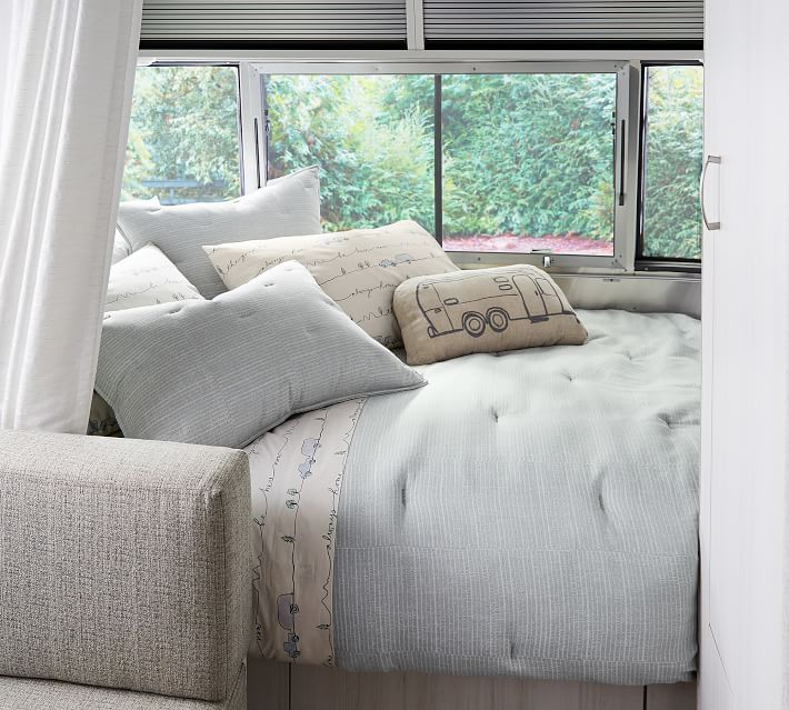 Comforter, shams, and sheet set from the 2021 Airstream X Pottery Barn  Collection displayed on an RV bed