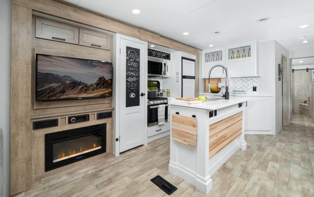 Keystone Arcadia travel trailer interior showing fireplace, kitchen island, and TV.
