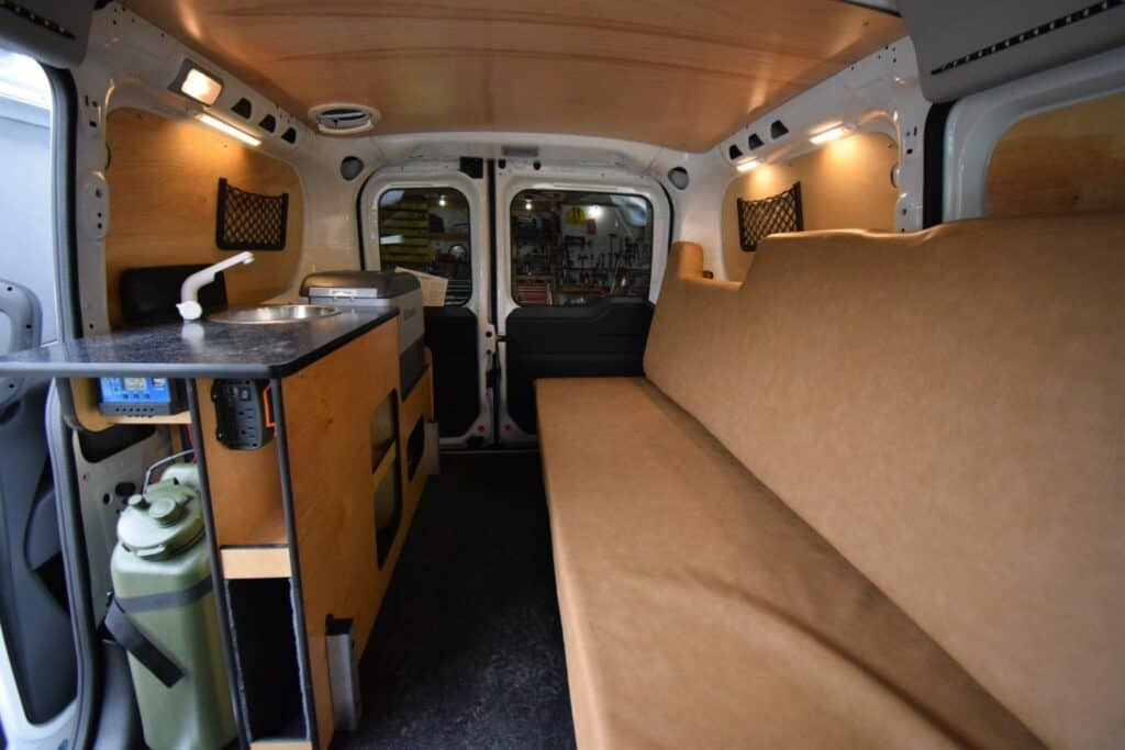 Interior of Cascade campers van conversion, view from the passenger's seat, featuring a couch, kitchen area with sink, water tank and outlets.