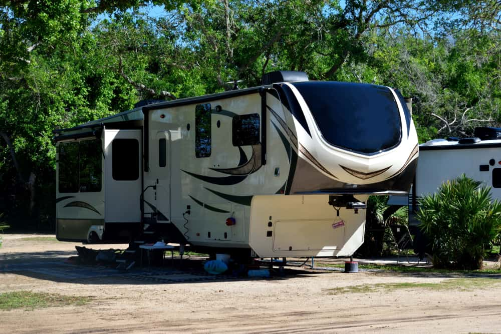 5th wheel camper with hitch exposed sits in campground.