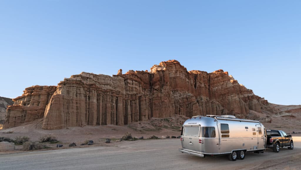 Airstream in front of a red rock landscape - protected by travel trailer roadside assistance