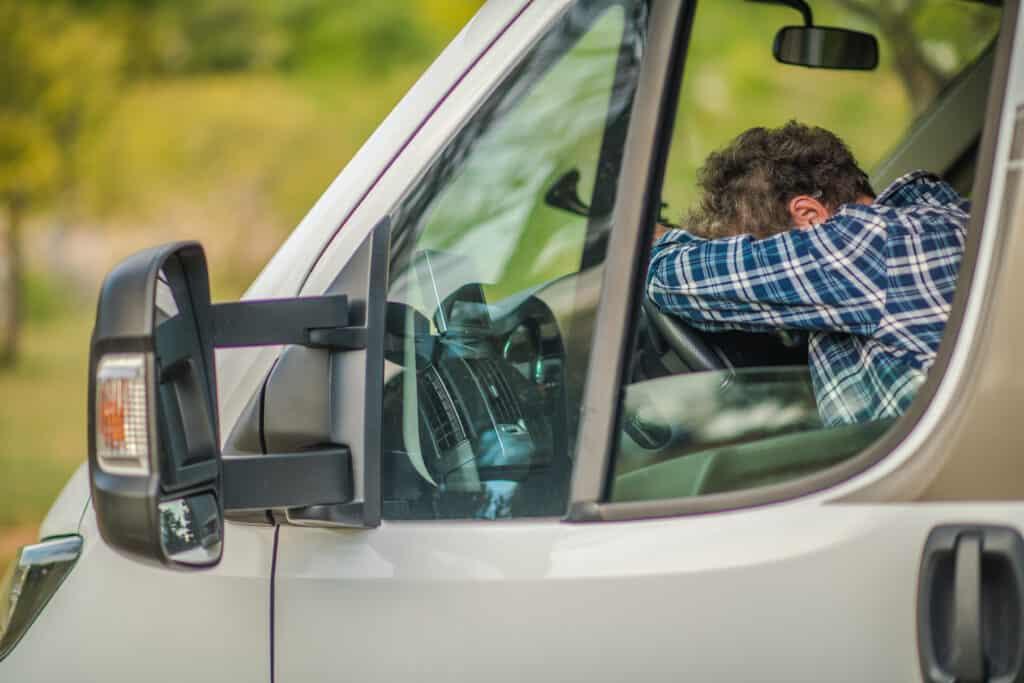 tired camper leaning on steering wheel