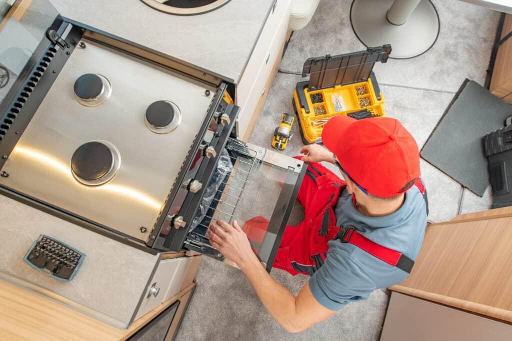 Top view of technician repairing oven in an RV.