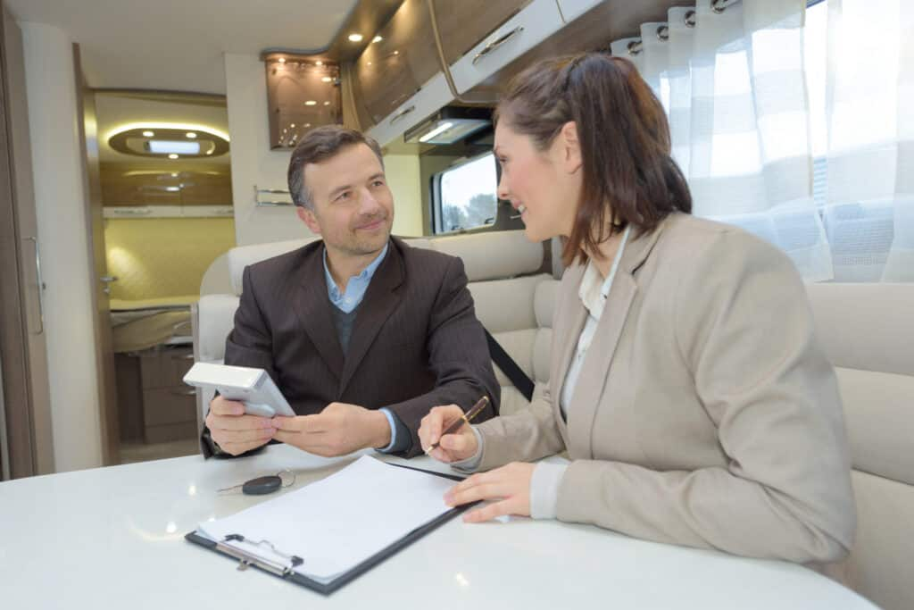sales people inside an RV sitting at table