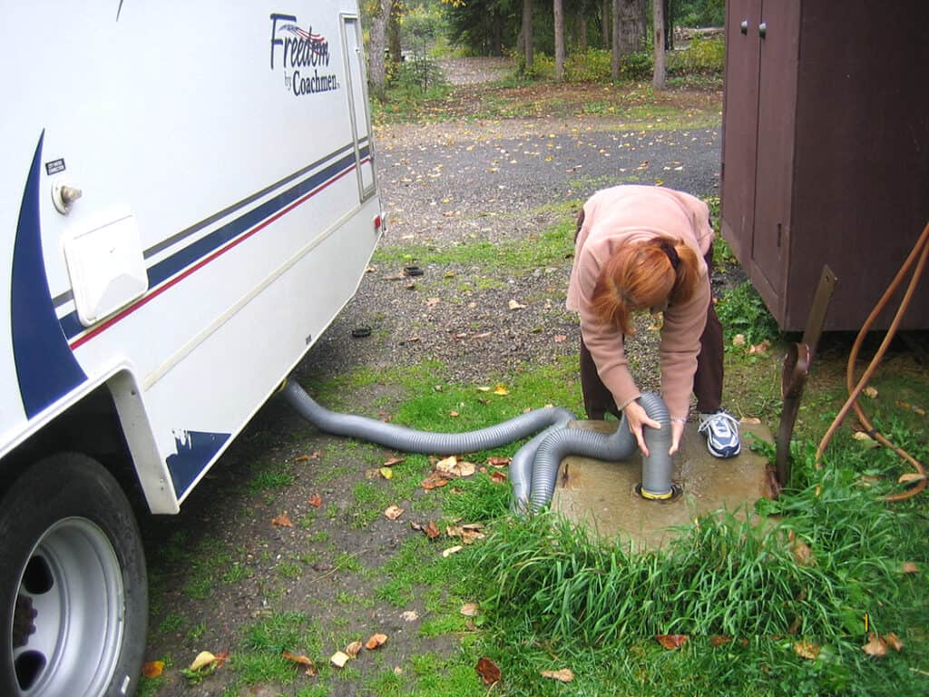 Woman with sewer hose and RV at a dump station.