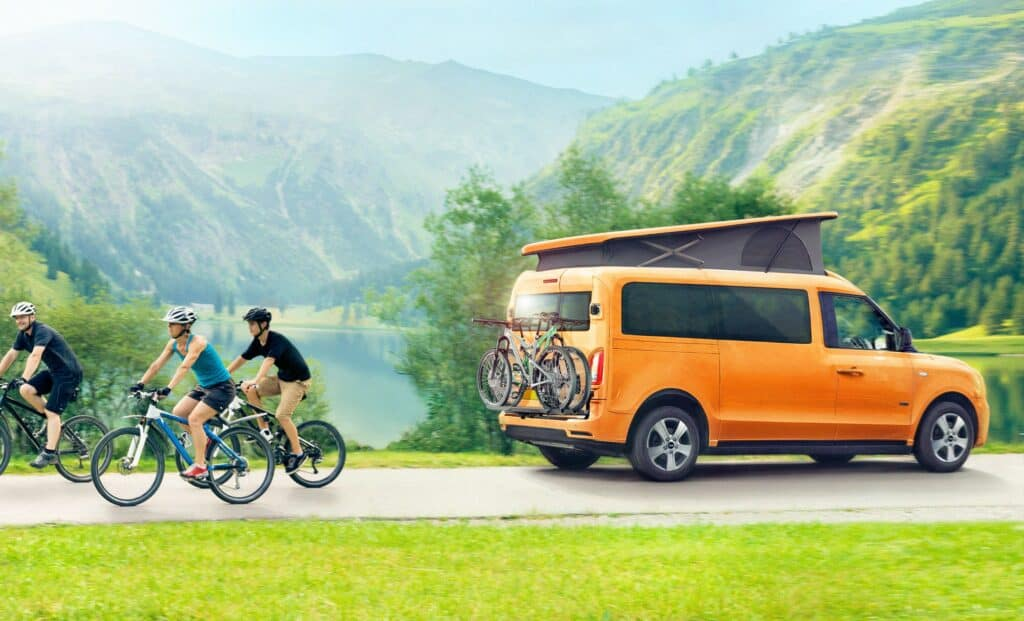 LEVC new e-Camper. Orange e-Camper with pop up roof extended and bicycles mounted on the back