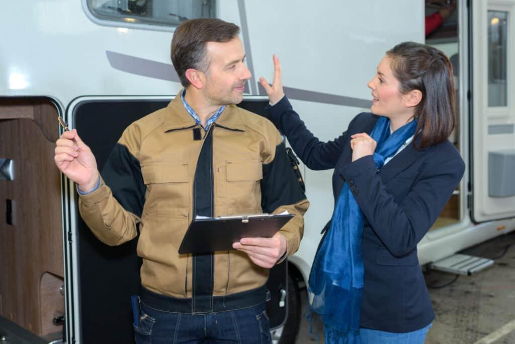 Women standing next to an RV asks technician about RV warranty items.