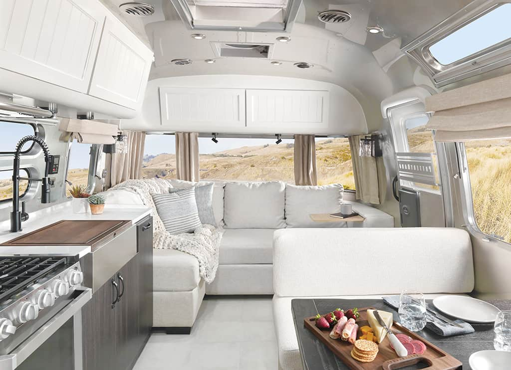 Interior view of the Airstream Pottery Barn Special Edition travel trailer featuring L-shaped sofa, kitchen and dining area