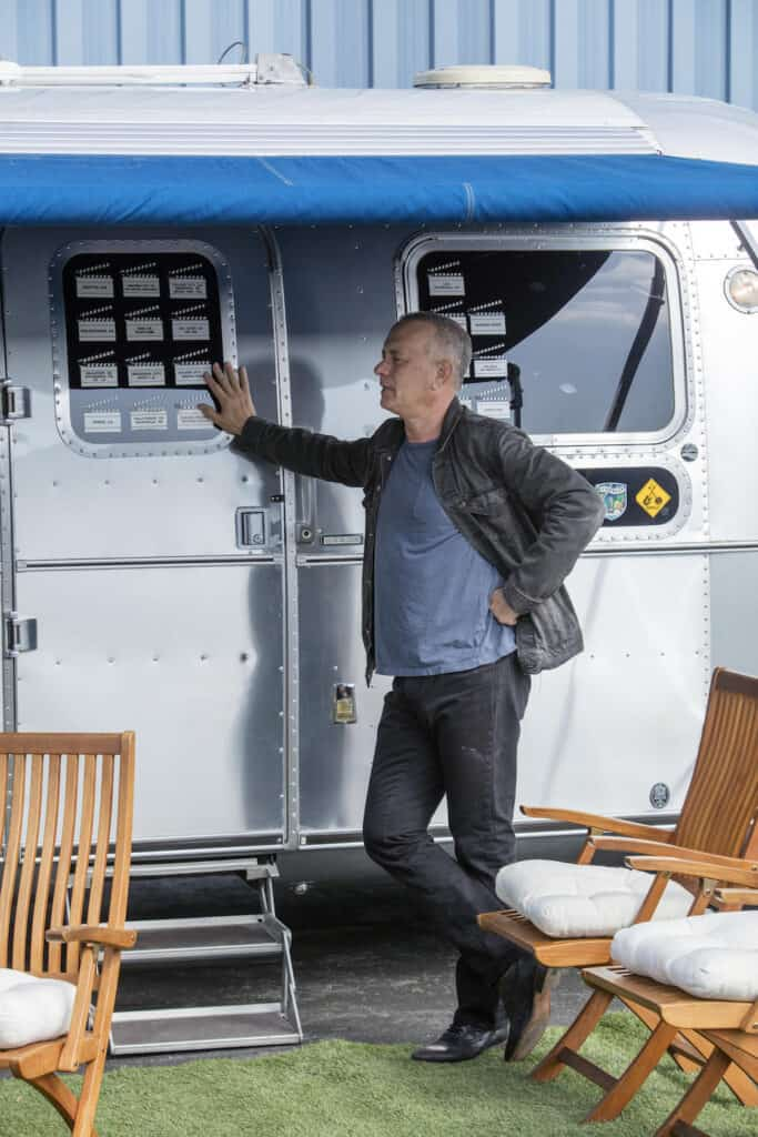 Tom Hanks standing at the door of his 1992 Airstream Travel Trailer before sending it to auction