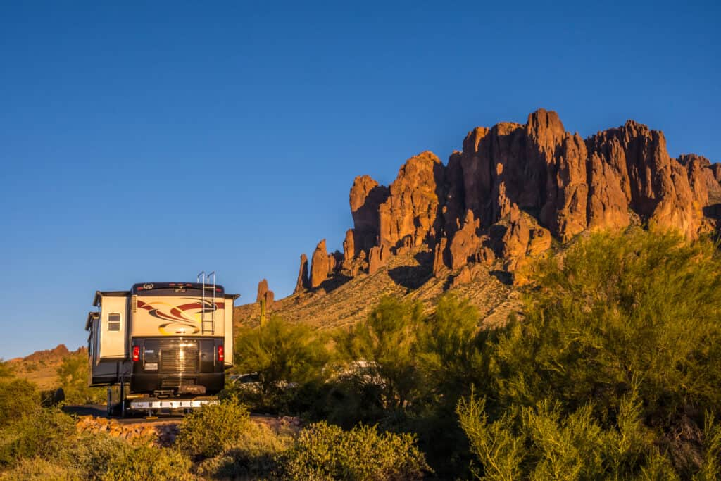 motorhome at campsite with rocky cliff - can you rent to own an RV?