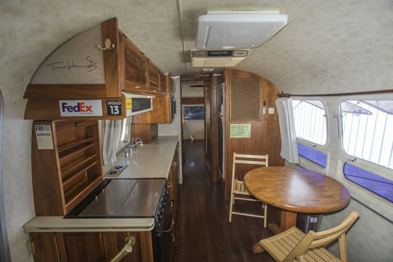 Interior features of Tom Hanks' Airstream Travel trailer featuring a kitchen, dining table, and back bedroom area